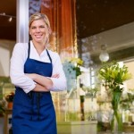 woman in apron outside store front
