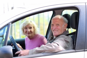 Happy senior couple driving modern car on their vacation trip