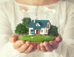 Woman holding small house, estate planning attorney