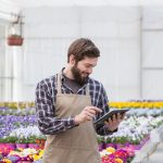 worker in flower shop on a tablet