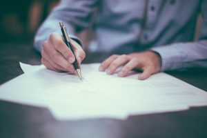 A man is signing papers, estate probate process