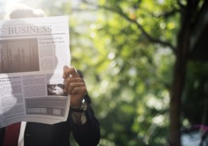 a man reading business newspaper, commercial attorney