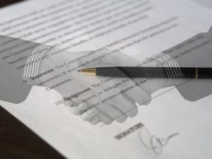 two people signing an agreement, business law attorney