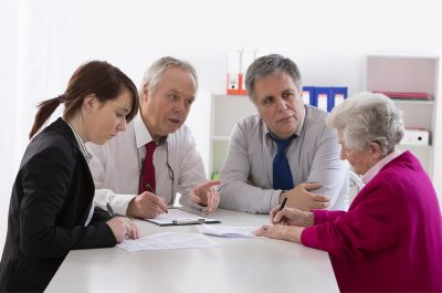 A groups of professionals are talking to a senior
