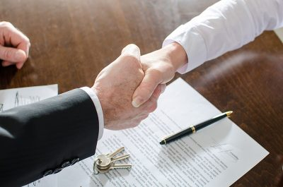 Business people shaking hands, signing documents with keys