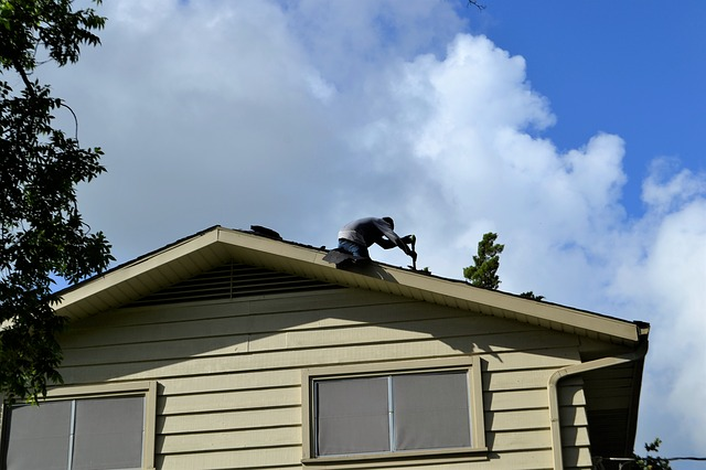 A man is fixing the roof of a house