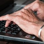 Senior's hands typing on a computer keyboard