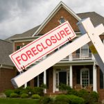Leaning foreclosure sign in front of a modern home