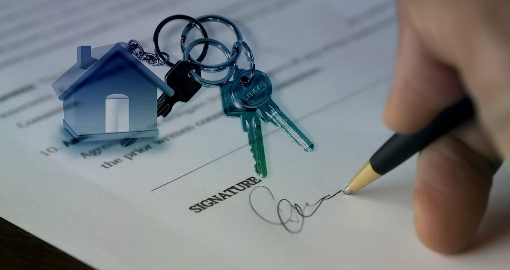 Signning a home sale contract, house key chain