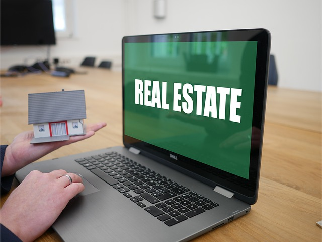 A person holds a house model and real estate words shown on a computer screen