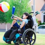 Boy in wheelchair playing a ball